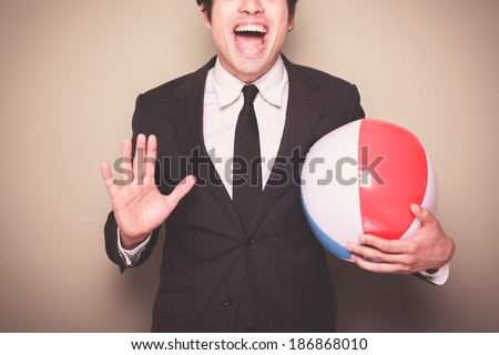 A young businessman is standing and holding a beach ball - stock photo