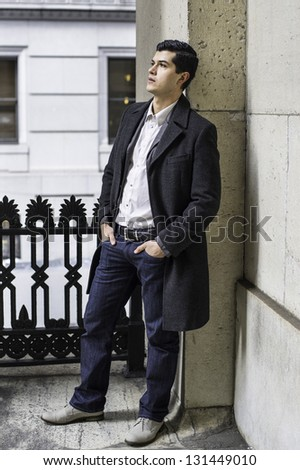A young businessman is standing outside the office building and taking a break. - stock photo