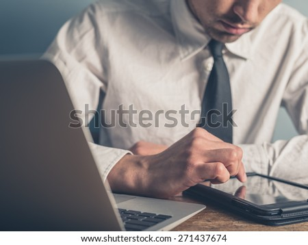 A young businessman is using a tablet while typing on a laptop computer - stock photo