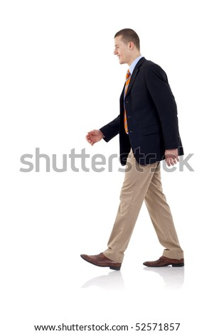 A young businessman is walking. He is smiling and looking away from the camera. isolated over white background