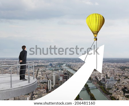 A young businessman looking at speeding up of company's profit, skyline city view  - stock photo