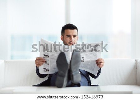 A young businessman on sofa reading newspaper in the office