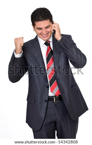A young businessman on the phone, with a fist in the other hand. He's excited abot the good news he's receiving on the phone. - stock photo