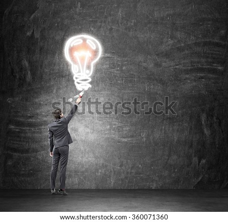 A young businessman painting a huge shining bulb with a brush on the black background. Back view. Concept of a new idea. - stock photo