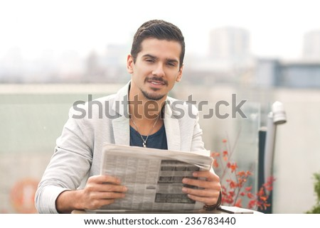 A young businessman reading a newspaper outdoors - stock photo