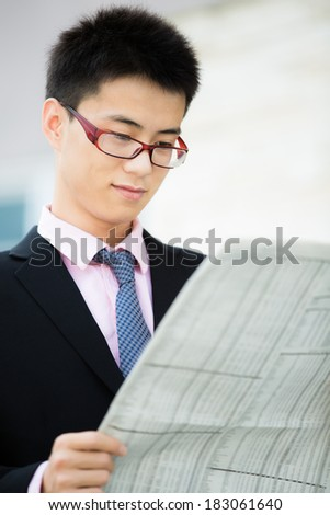 A young businessman reading newspaper outdoors