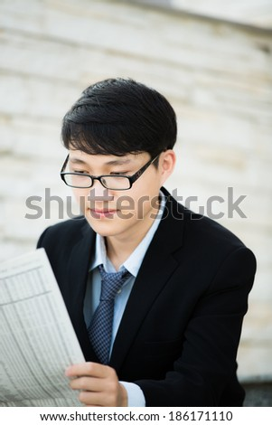 A young businessman reading newspaper outdoors - stock photo