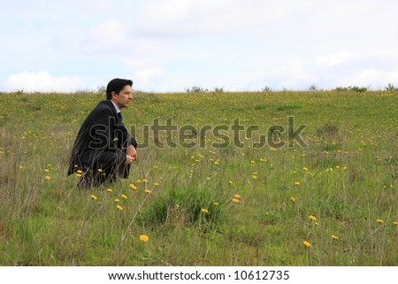 A young businessman sitting in a field thinking about a solution - stock photo