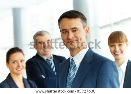 A young businessman smiling against three partners