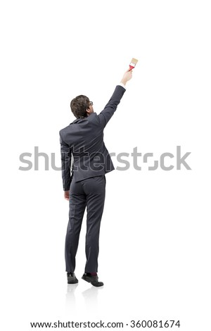 A young businessman starting to draw something on a blank white wall with a brush, Back view. Concept of a new start. - stock photo
