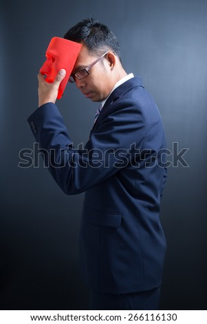 A young businessman take off the mask. - stock photo