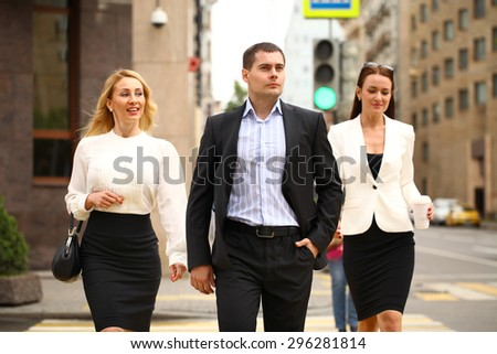 A young businessman walking on the street with their secretaries, outdoor summer street