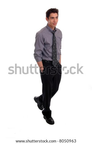 A young businessman walking with hands in pockets