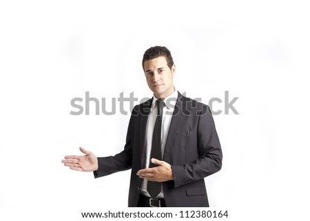A young businessman with a tie presents something on his right