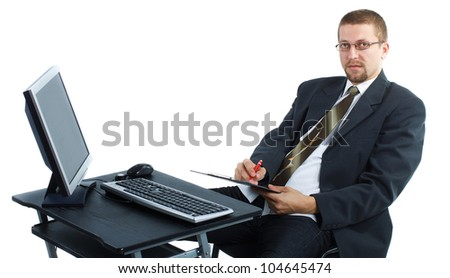 A young businessman with glasses, suit and tie is sitting by his desk with computer and writing on clipboard, looking into the camera - isolated on white - stock photo