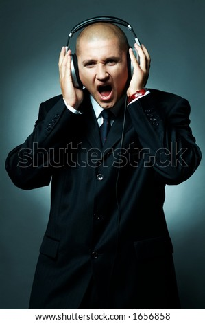 A Young businessman with headphones listen to the music