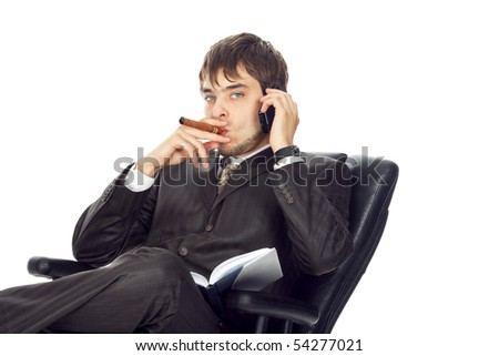 a young businessman with mobile phone sitting in a chair and smoking a cigar isolated on white - stock photo