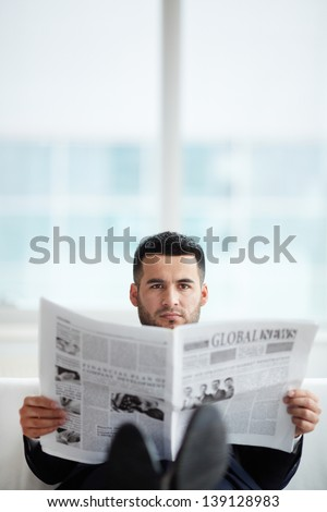 A young businessman with newspaper looking at camera