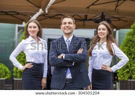 A young businessman with their secretaries, outdoor summer street - stock photo