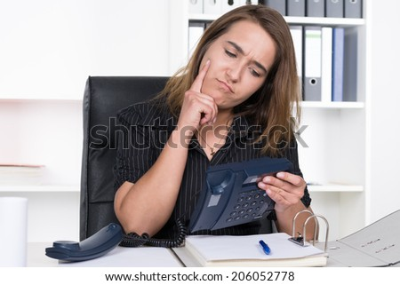 A young businesswoman is sceptically looking at a telephone which she is holding in her hand while sitting at the desk in the office. A shelf is standing in the background.