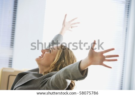 A young businesswoman is sitting in an office with her hands outstretched in the air. Horizontal shot.