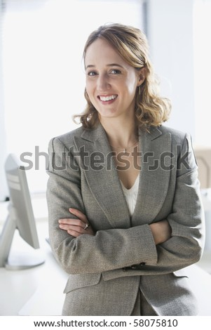 A young businesswoman is sitting on an office desk and smiling at the camera.  Vertical shot.