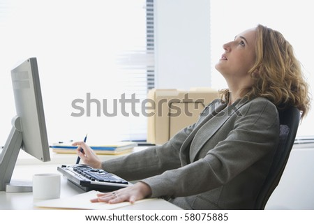 A young businesswoman leans back in her chair with a pensive expression on her face.  Horizontal shot.
