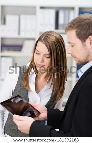 A young businesswoman looks at a male colleagues tablet as he shows her a blank screen visible to the viewer as they stand together in the office - stock photo