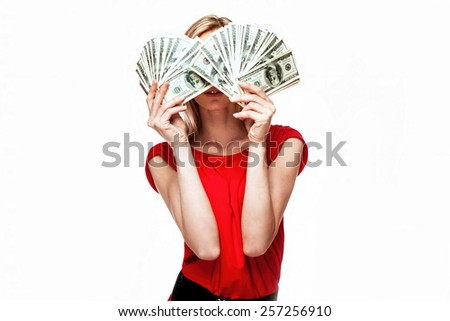 A young businesswoman with dollars in her hands isolated on white background - stock photo