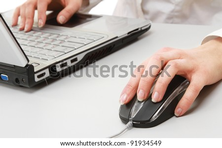 A young businesswoman working on a laptop, focus on her hands