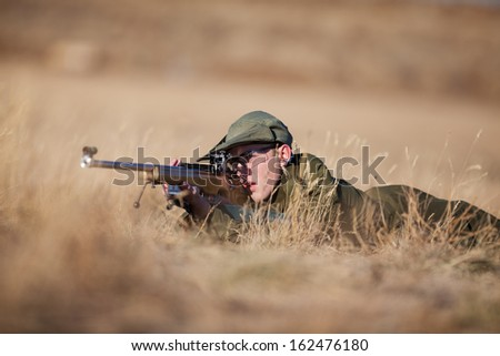 A young cadet laying in the dry grass target shooting. - stock photo
