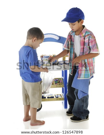 A young candy entrepreneur placing a sucker in his customer's bag.  On a white background. - stock photo