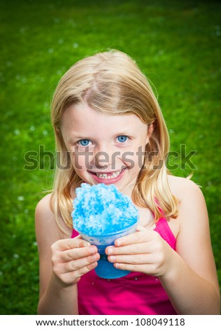 A young Caucasian blond girl holds a blue snow cone as she smiles at the camera. - stock photo