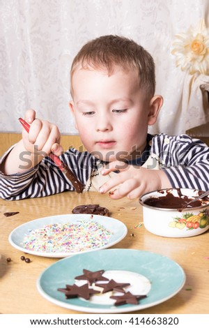 a young caucasian boy decorating cookies  - stock photo