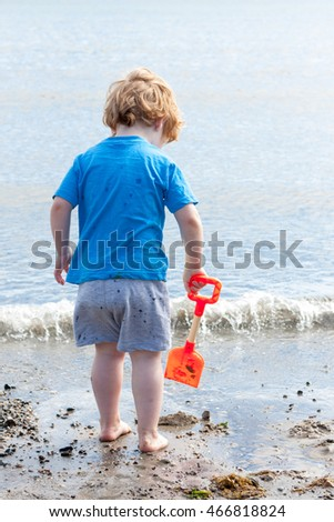 A young caucasian boy holding an orange spade next to the sea on a beach