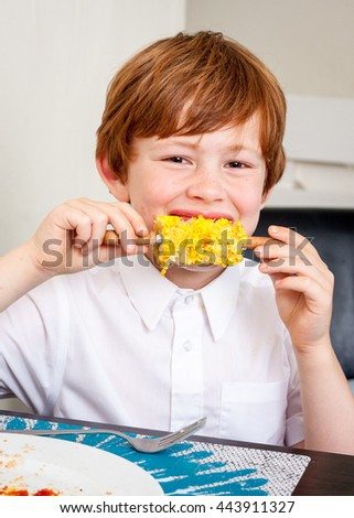 A young caucasian boy looking at the camera and smiling whilst eating corn on the cob