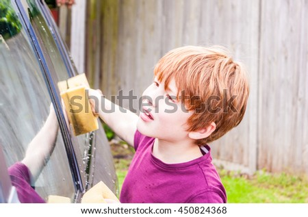 A young caucasian boy looking deep in concentration whilst washing a car
