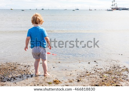 A young caucasian boy looking out to sea