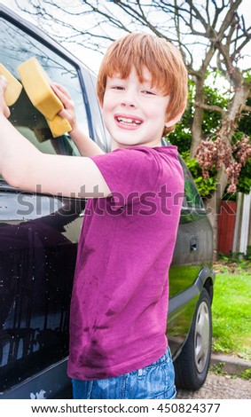 A young caucasian boy looking straight at the camera and smiling whilst washing a car