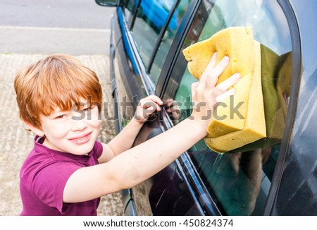 A young caucasian boy looking straight at the camera and smiling whilst washing a car with a yellow sponge