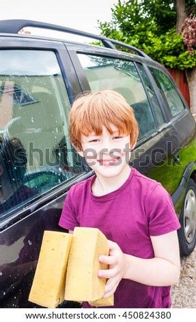A young caucasian boy looking straight at the camera holding two sponges to wash a car