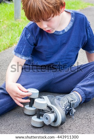 A young caucasian boy sat down outside looking at the roller-skates he is wearing - stock photo