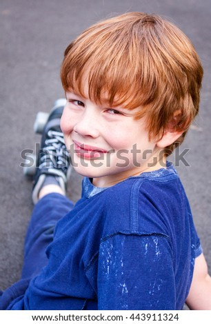 A young caucasian boy sat down outside wearing a pair of roller-skates looking at the camera - stock photo