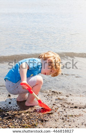 A young caucasian boy using an orange toy spade to dig on a beach