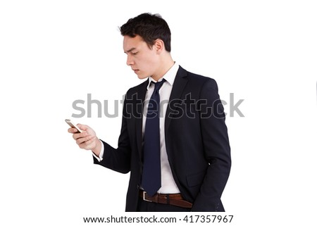 A young Caucasian business man is looking at his mobile phone. His finger is on the screen operating the smart phone.