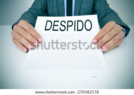 a young caucasian businessman in grey suit sitting at his office desk shows a document with the text despido, dismissal in spanish, written in it - stock photo