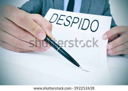 a young caucasian businessman sitting at his office desk shows a document with the word despido, dismissal written in spanish, and points with a pen the spanish word firma, signature - stock photo