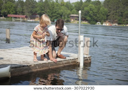 A young caucasian child feeds fish from a dock on a Minnesota lake with her father - stock photo