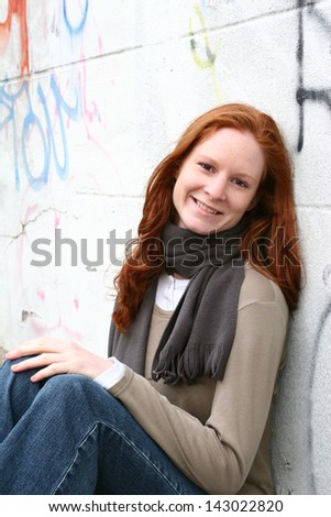 A young Caucasian female with red hair posing next to a graffiti wall in an urban setting. - stock photo