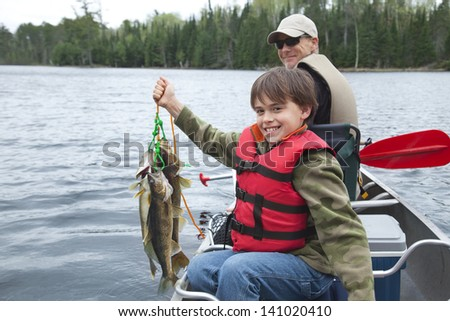 A young caucasian fisherman proudly holds up a stringer of walleyes  - stock photo
